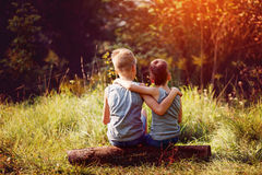 Two little boys friends hug each other in summer sunny day. Brother love. Concept friendship. Back view.  Stock Photo
