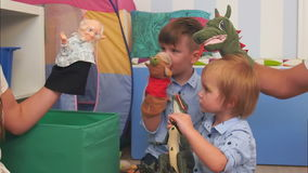 Two little boys having fun playing with hand puppets. Close up. Slow motion shot. Professional shot in 4K resolution. 092. You can use it e.g. in your stock video