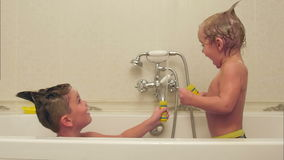 Two little boys having fun while taking bath in bathtub stock video footage