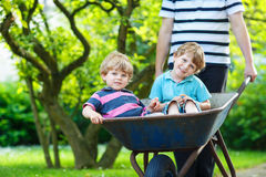Two little boys having fun in wheelbarrow pushing by father Royalty Free Stock Photography
