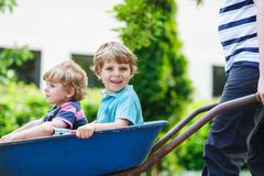 Two little boys having fun in a wheelbarrow Royalty Free Stock Image