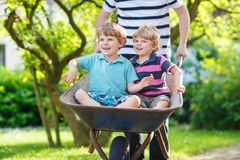 Two little boys having fun in wheelbarrow pushing by father Royalty Free Stock Photos
