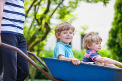 Two little boys having fun in a wheelbarrow pushing by father in Royalty Free Stock Photography