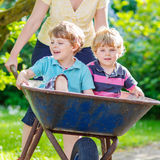 Two little boys having fun in a wheelbarrow pushing by mother Stock Photos