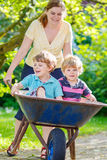 Two little boys having fun in a wheelbarrow pushing by mother Royalty Free Stock Photos