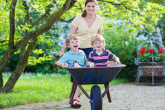 Two little boys having fun in a wheelbarrow pushing by mother Royalty Free Stock Photography