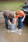 Two little boys helping wash the car stock images