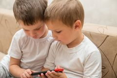 Two little boys holding smartphone royalty free stock image