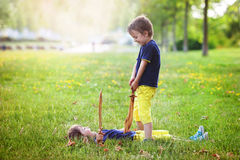 Two little boys, holding swords, glaring with a mad face at each. Other, fighting outdoors in the park stock photos