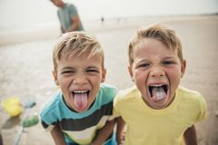 Little Boys Sticking their Tongues Out. Two little boys looking at the camera being cheeky and sticking their tongues out Royalty Free Stock Photos