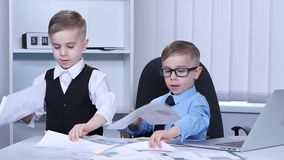 Two little boys looking graphics and scatter on the table. Slow motion stock video