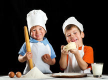 Two little boys making pizza or pasta dough Stock Photos