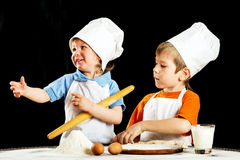 Two little boys making pizza or pasta dough Stock Image
