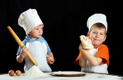 Two little boys making pizza or pasta dough Stock Images