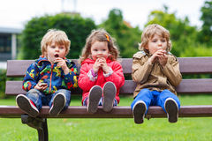 Two little boys and one girl eating chocolate. Three children: two little boys and one girl sitting on bench and eating chocolate Stock Photos