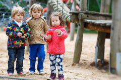Two little boys and one girl playing with soap bubbles. Three children: two little boys and one girl playing with soap bubbles on playground Royalty Free Stock Image