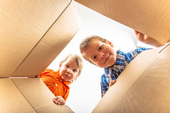 Two little boys opening cardboard box and looking Stock Images