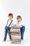 Two little boys with a pile of books Stock Photos