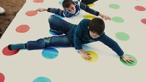 Two little boys play funny twister game on street. Summer festival. Sunny day. Two little boys play huge popular funny twister game on street. Summer festival stock footage