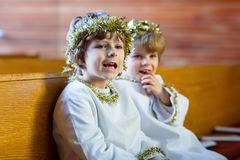 Two little boys playing an angel of Christmas story in church Royalty Free Stock Image