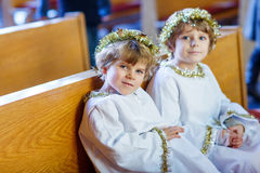 Two little boys playing an angel of Christmas story in church Stock Images