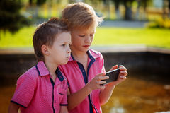 Two little boys playing games on mobile phone in sunny day. Royalty Free Stock Images