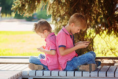 Two little boys playing games on mobile phone in sunny day, sitt Stock Image