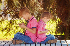Two little boys playing games on mobile phone in sunny day, sitt Royalty Free Stock Photo