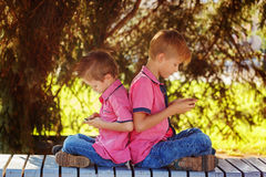 Two little boys playing games on mobile phone in sunny day, sitt Stock Photography