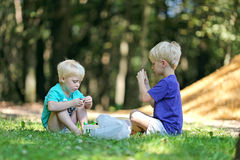 Two Little Boys Playing Outside in Dirt. Two little boys are playing outside in the woods, with toys and dirt on a summer day royalty free stock image