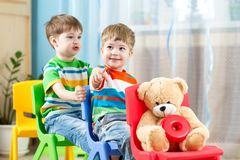 Two little boys playing role game in daycare stock images