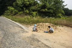 Two little boys playing with sand on the farm. Taken in the old village of Pukou, Jiangbei, Nanjing, Jiangsu, China royalty free stock photos
