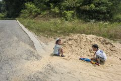 Two little boys playing with sand on the farm. Taken in the old village of Pukou, Jiangbei, Nanjing, Jiangsu, China royalty free stock photo