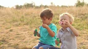 Two little boys playing with soap bubbles in Park. Two little boys playing with soap bubbles in the Park at sunset, slow motion stock video