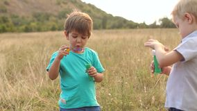 Two little boys playing with soap bubbles in Park. Two little boys playing with soap bubbles in the Park at sunset, slow motion stock footage