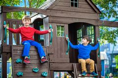 Two little boys playing together and having fun. Lifestyle family moment of siblings on playground. Kids friends play on tree. House climbing on rope or stairs stock photography