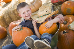 Two Little Boys Playing in Wheelbarrow at the Pumpkin Patch Royalty Free Stock Photo