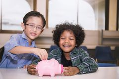 Two little boys putting money into piggy bank for future savings. Tow little boys putting money into piggy bank for future savings, multicultural together Royalty Free Stock Image