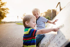 Two little boys reading outdoor map. Warm spring day. Two cute little boys reading outdoor map. Warm spring day Royalty Free Stock Image
