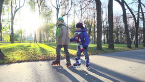 Two little boys ride in autumn park on rollerblades. Slow motion stock footage