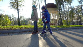 Two little boys ride in autumn park on rollers. Slow motion stock video footage