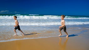 Two little boys running on a sandy beach on sunny day stock footage