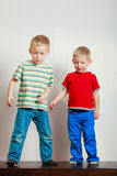 Two little boys siblings playing together on table Royalty Free Stock Photography