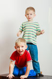 Two little boys siblings playing together on table Stock Photo