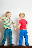 Two little boys siblings playing together on table Stock Photos