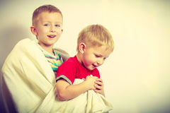 Two little boys siblings playing with towels Stock Image