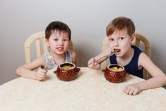 Two little boys sit at the table and eat roast chicken and potatoes Royalty Free Stock Image