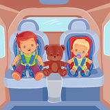 Two little boys sitting in child car seats Stock Photos