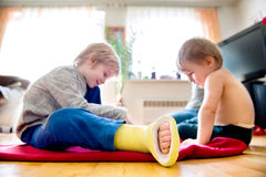 Two little boys sitting on the floor playing. Cute little blond boy with broken leg in cast with his little brother sitting on the wooden floor, playing Royalty Free Stock Image