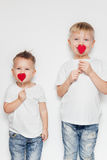 Two little boys standing with heart shape on a wooden sticks against white background Royalty Free Stock Photo